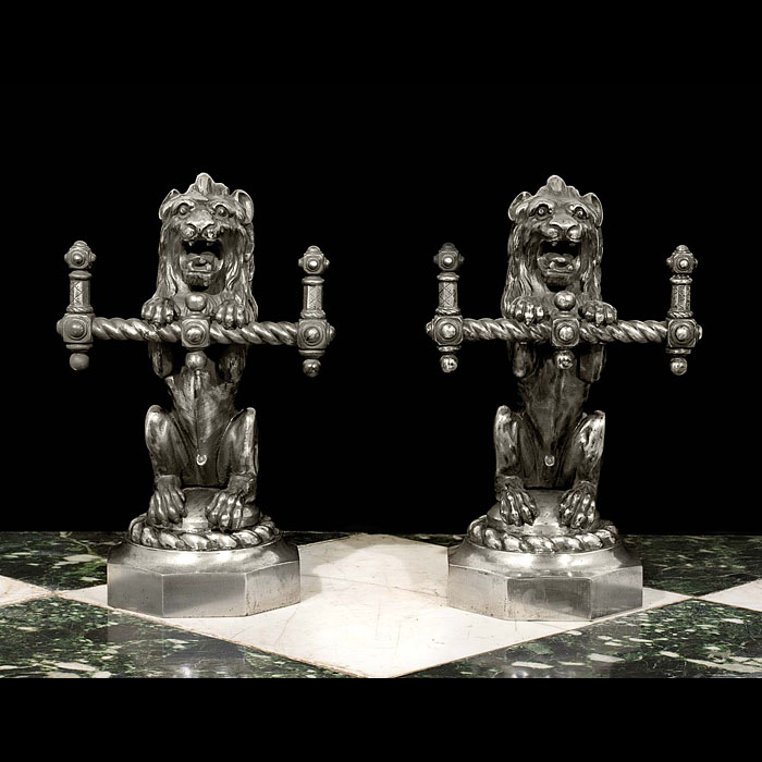 A pair of lion form antique firetool rests.