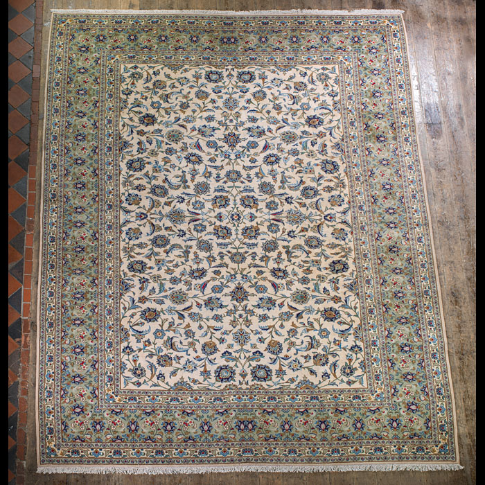 A large ivory, blue & magenta Kashan carpet